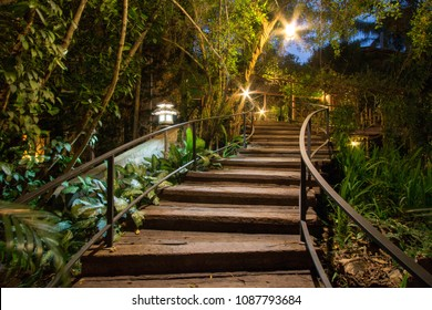 Wooden staircase in the woods at night. Lighting with lanterns.