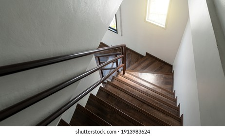 Wooden stairs in a bright modern two-story apartment with a window