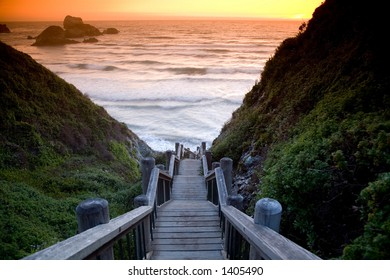 Wooden stairs leading to the beach at sunset with rock formations in the background.