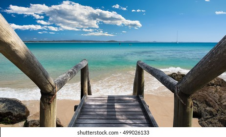 Wooden Stairs Leading To A Pristine Caribbean Beach Paradise Overlooking A White Sail Boat, People Kayaking And Paddle Boarding During A Beautiful Sunny Day, Sunshine Coast, Queensland, Australia