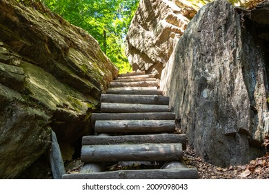 wooden stairs on a rocky path between rocky walls facing upwards