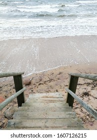 Wooden stairs that lead to a flooded beach coast. Baltic sea and weather during december storm. Northern country and it's coastal nature beauty.