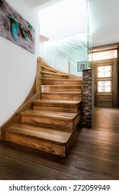 Wooden stairs with visible wood texture in bright daylight coming from the second floor. Stairs are lined with paneled stone wall and illuminated glass panel with a blue touch.