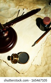 Wooden stamp, gavel and old papers, close up