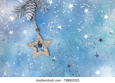 wooden star and fir-tree branch with cone on sparkling blue background