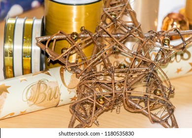 Wooden star in front of various materials such as wrapping paper and ribbons to pack and decorate Christmas presents.