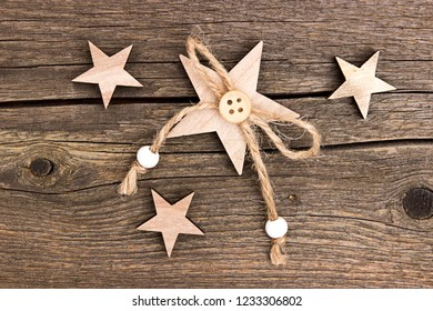 Wooden stars with a string of pearls and a button on a wooden background