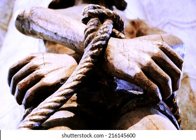 Wooden statue of Jesus with tied hands. Aged photo.