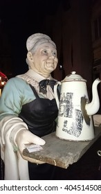 Wooden statue of old woman with traditional ceramic teapot, Romania