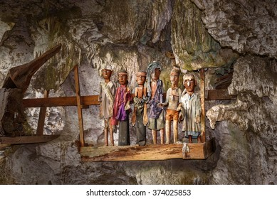 Wooden statues of Tau Tau in Tampang Allo burial cave of the royal family. There are pile of skulls by the entrance, coffins are placed in caves or hanging from cliff. Tana Toraja. Sulawesi. Indonesia