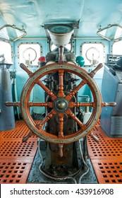 Wooden steering wheel in control cabin room.