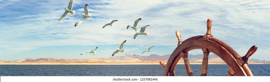 Wooden steering wheel on the sailboat - panorama of sea landscape with mountain seashore and flying birds. Wide view skyline with captains helm on sailling ship and seagulls over for marine concept.