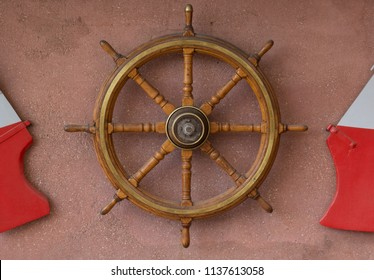 A wooden steering wheel from a sea ship hanging on a wall. Decoration for a wall