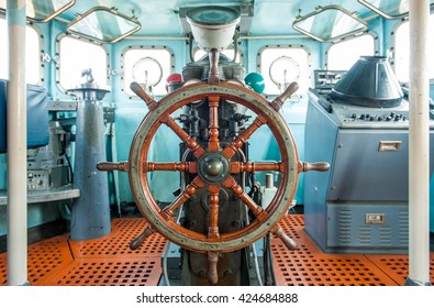 Wooden steering wheel in ship control cabin room.