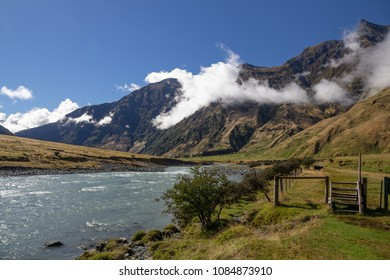 Wooden steps over fence, green, fertile valley with cows grazing in nearby fields and glacial river flowing briskly downstream is fitting start and end for Rob Roy Glacier Track in New Zealand