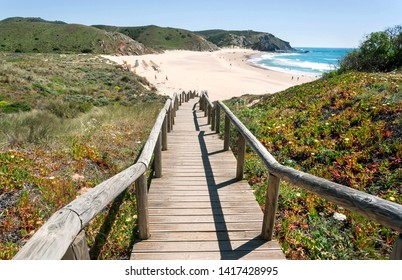 Wooden steps to the sunny beach in Portugal town. Ocean waters and green hills over peaceful seaside at sunny day of Algarve area.