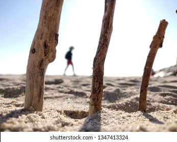 Wooden sticks stuck in beach sand with girl walking in background.