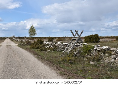 Wooden stile by a dirt road in a great plain grassland, a world heritage site at the swedish island Oland