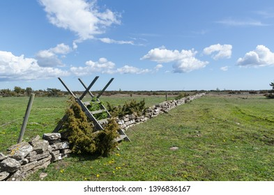 Wooden stile by a dry stone wall in spring season at the great plain grassland and world heritage sita Alvaret at the swedish island Oland