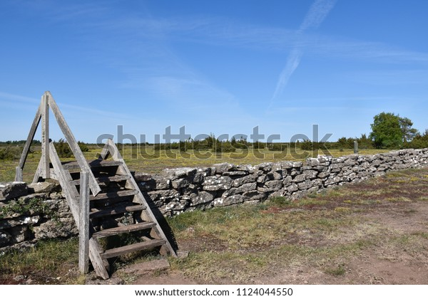 Wooden stile by a dry stone wall at the great alvar plain on the swedish island Oland