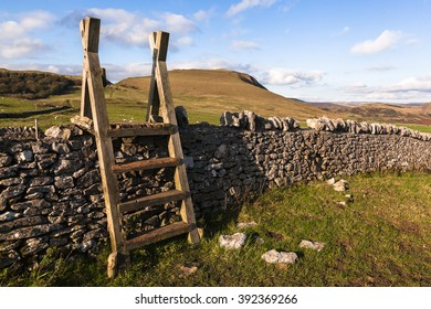 A wooden stile over a limestone dry-stone wall in the Peak District, Derbyshire, England UK. There are hills, sheep and trees in the background with a lightly clouded blue sky.