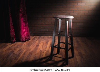 wooden stool on a stand up comedy stage with reflectors ray, high contrast image