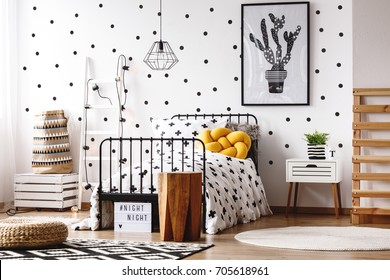 Wooden stool in scandinavian style kids room with knot yellow pillow on bed with black and white coverlet