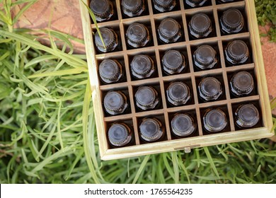 Wooden storage box full of glass amber essential oils bottles. Top down with no labels visible