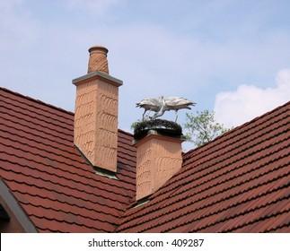 Wooden Storks on Roof