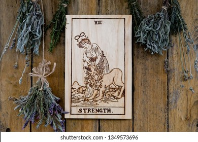 Wooden Strength card from Tarot Major Arcana with dried herbs on rustic background - hand burnt in wood by photographer