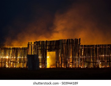 Wooden structure on fire with small sparks flying around.