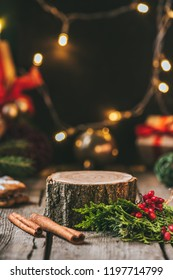 wooden stump with cinnamon sticks, fir tree and christmas light garland