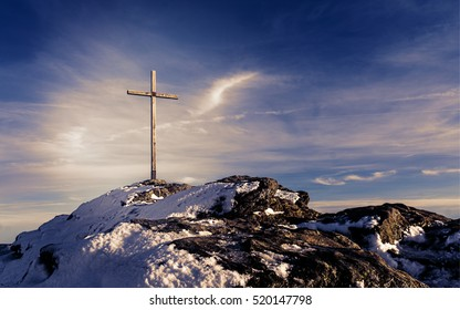 Wooden summit cross on the mountain peak with cloudy clear sky - Picture with mystic purple look