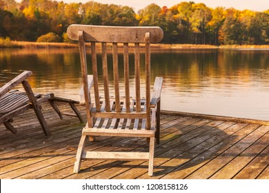 Wooden sunloungers by lake in autumn.