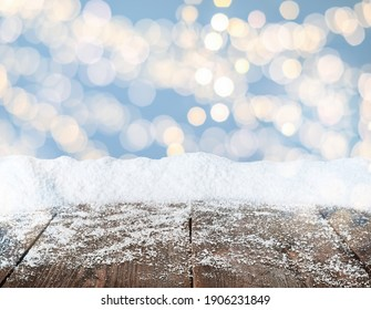 Wooden surface with heap of snow and blurred Christmas lights on background, bokeh effect