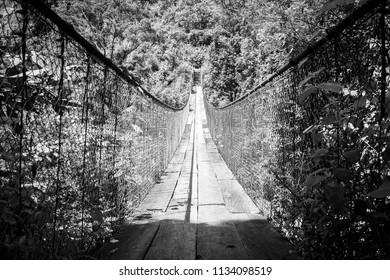 Wooden suspension bridge over river in Panajachel, Guatemala, Central America in black and white
