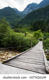 Wooden suspension bridge over the stream of fresh alpine water and beautiful forest with mountainous landscape in background. Hiking, travel, nature and tourism concepts
