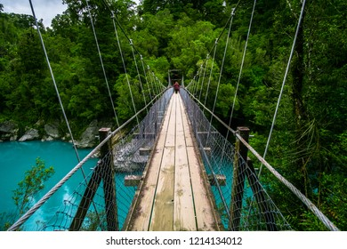 The wooden swing bridge in the green nature.