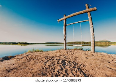 A wooden swing by a lake at the Finnish Lapland. It's quite late, but there is still plenty of light on the nightless nights of the Northern summer.