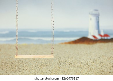 A wooden swing in the foreground on a sandy beach with a blurred lighthouse and waves crashing in the background.  A light blue blank sky area could be used for text.
