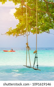 Wooden swing hanging on a branch of tree at the turquoise sea, ThailandExotic tropical paradise swings over crystal blue ocean sea with kayak landscape.
