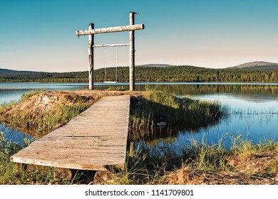 A wooden swing has been set up on a little island in a lake at the Finnish Lapland. The swing is a perfect place to admire the beautiful lake and the nightless night.