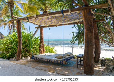 Wooden swing with a mattress and pillows under a canopy on the tropical beach near sea, island Zanzibar, Tanzania, East Africa, travel and vacation concept