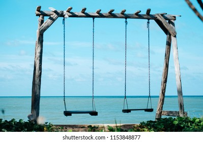 Wooden Swing on the beach with blurred of sea background