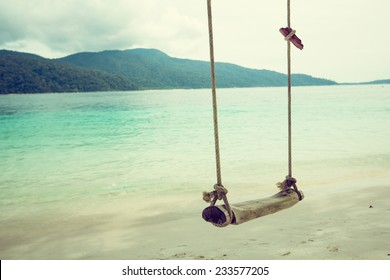 Wooden swing on beautiful white sand tropical beach, Thailand. retro filter.