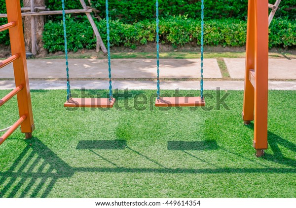 Wooden swing swing, Set of chain swings on modern kids playground with Green Artificial grass,Idea for shop decoration.