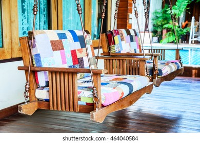 Wooden swinging bench , Wooden porch swing bench, Relaxing hammock in the garden.
