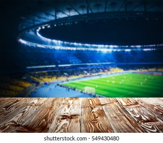 Wooden table against football stadium background