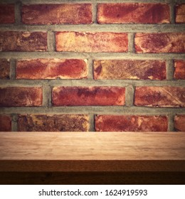 Wooden table against red brick wall, rustic background