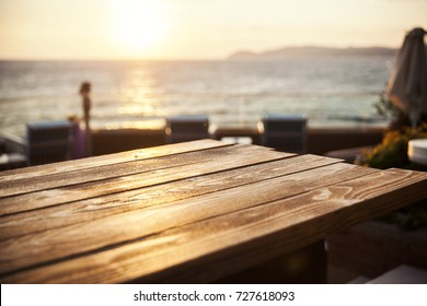 wooden table against sunset on sea, close up